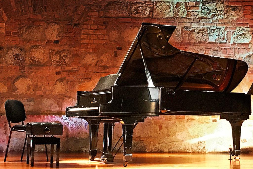 black grand piano in basement style bar